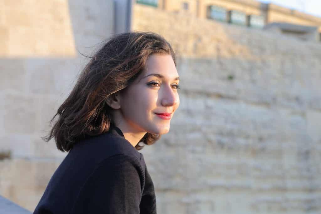 Mulher de cabelos curtos vista de perfil, sorrindo sem mostrar os dentes