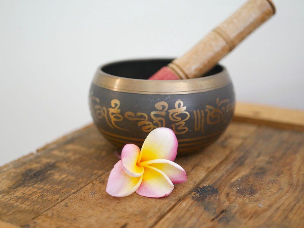 Imagem de um pote oriental para macerar florais para uso em terapia floral. Ao lado do pote uma flor de lótus.