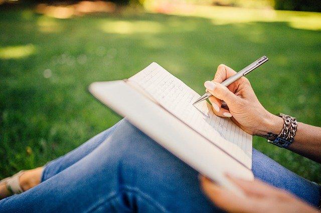 Mulher sentada em grama, com os joelhos levemente flexionados, e um caderno apoiado neles. Ela escreve no caderno com uma caneta.