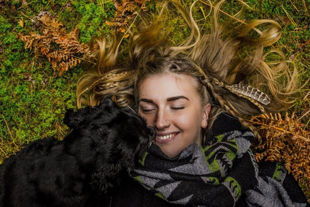 Mulher deitada no gramado ao lado de seu cãozinho