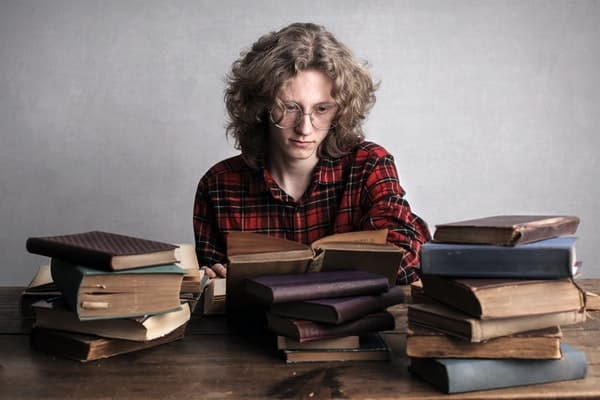 Garoto sentado com livros antigos sobre a mesa