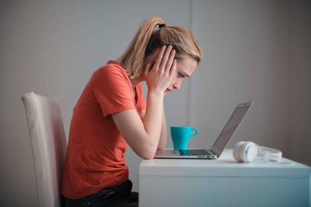 Mulher sentada em uma mesa de trabalho, com expressão triste e apoiando a cabeça sobre os braços.
