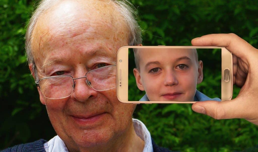Imagem do rosto de um senhor de idade usando óculos, porém a imagem dele refletida na tela do celular é dele em sua infância.