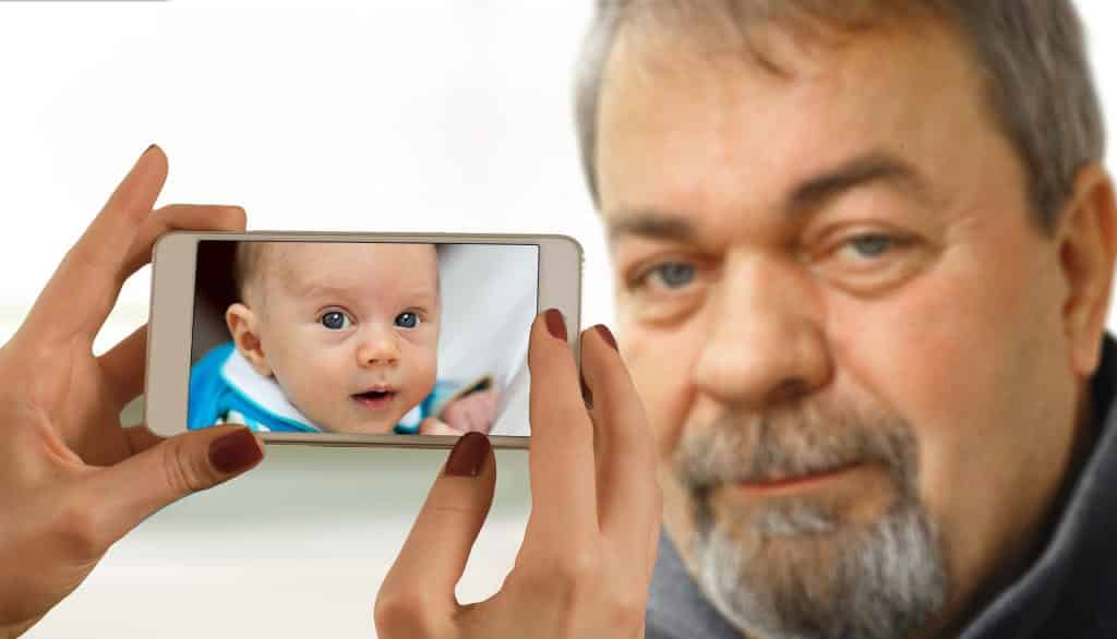 Imagem do rosto de um senhor grisalho e olhos azuis. Ele usa cavanhaque e bigode. As mãos de uma mulher segura o celular e a imagem que reflete na tela é de um bebê se referindo ao senhor quando criança.