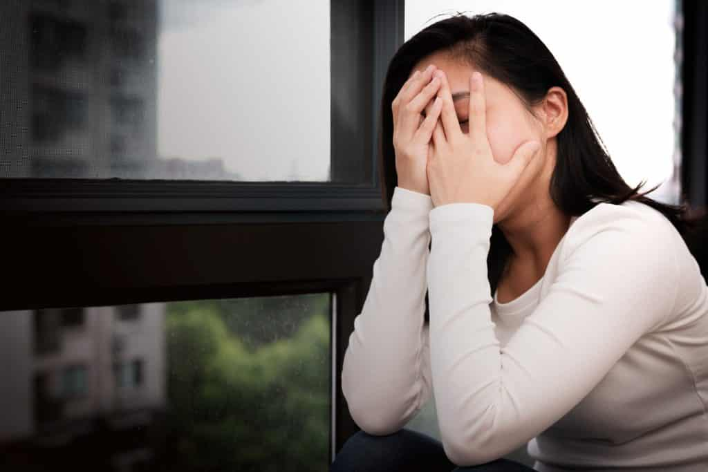 Mulher com as mãos no rosto ao lado de uma janela