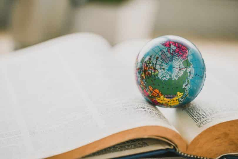Mini globo terrestre em cima de livro aberto