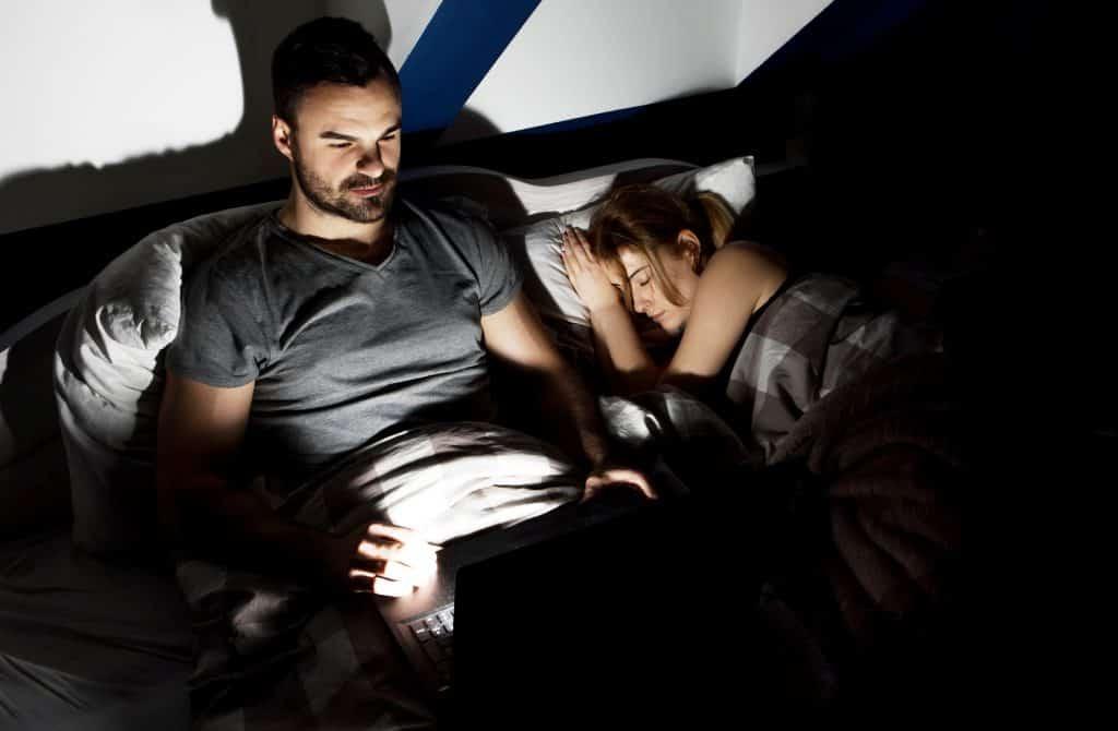 Homem deitado em cama, com mulher dormindo ao seu lado. Ele está acordado, e usando um notebook em seu colo.