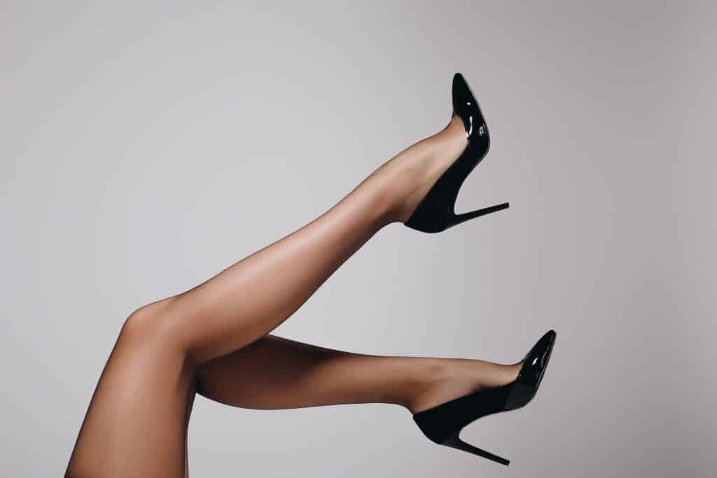 Imagem das pernas nuas de uma mulher. Ela um salto preto,
