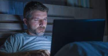 Homem deitado, no escuro, com um notebook em seu colo.