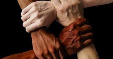 Mãos segurando no pulso de outras de todas as cores
