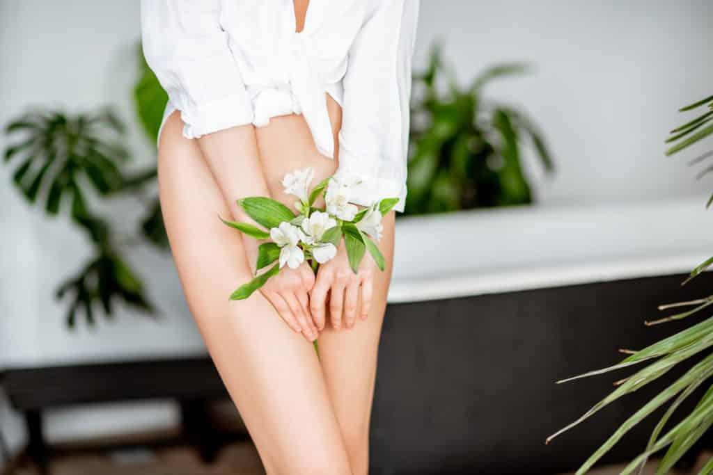 Imagem do corpo de uma mulher - do pescoço para baixo - ela usa uma camisa de mangas longas na cor branca. Está sem as roupas de baixo e segura entre as mãos um ramo de flores logo abaixo da barriga.