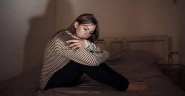 Mulher sentada na cama com celular na mão pensativa