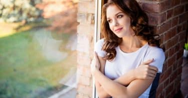 Mulher olhando pela janela enquanto abraça a si mesma.