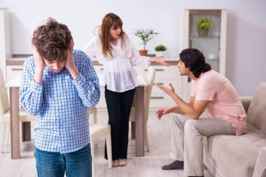 Pais discutindo ao fundo e criança na frente tampando os ouvidos.