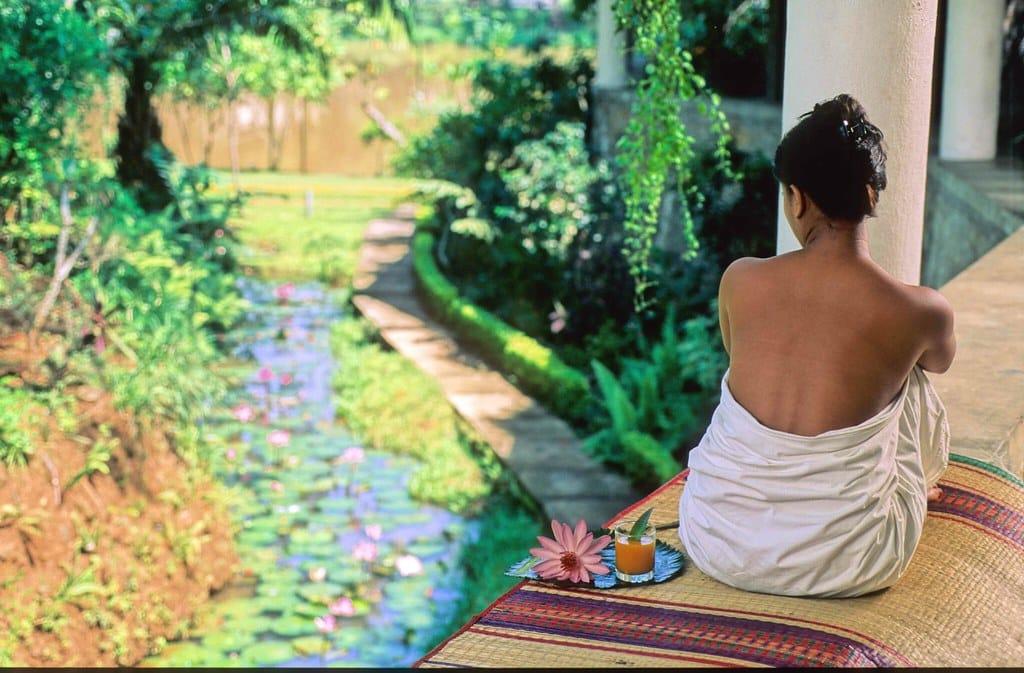 Mulher sentada em um parque, com suco e flores, durante sessão de Ayurveda.