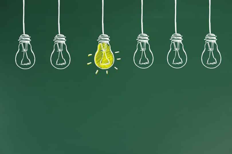 Lâmpadas desenhadas lado a lado em um quadro verde, e uma delas está preenchida de amarelo, como se estivesse acesa.