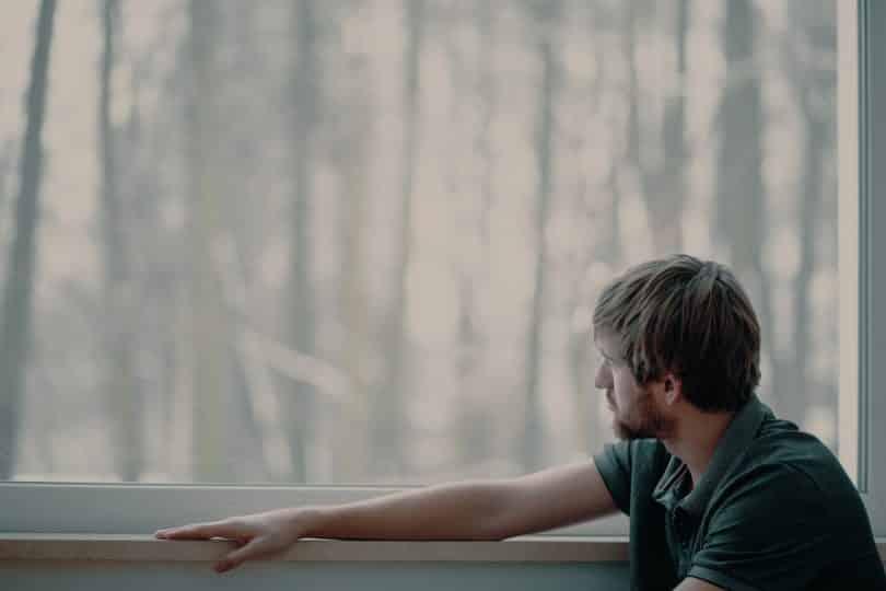 Homem sentado à janela observa-a.