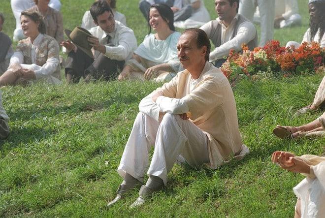 Homem sentado no gramado com outras pessoas ao redor