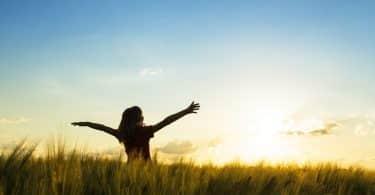 Mulher com braços abertos com mato e céu azul ao fundo