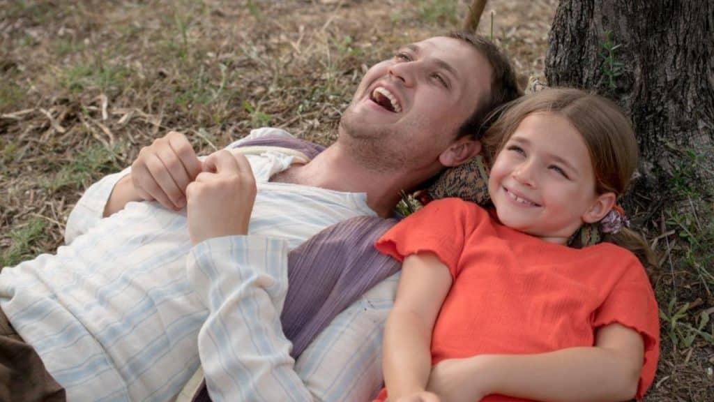 Homem e criança deitados no pé da árvore sorrindo e olhando para cima