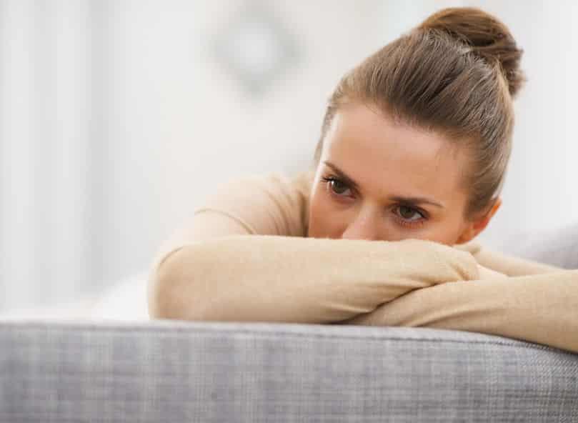 Mulher apoiada em sofá com olhar tenso