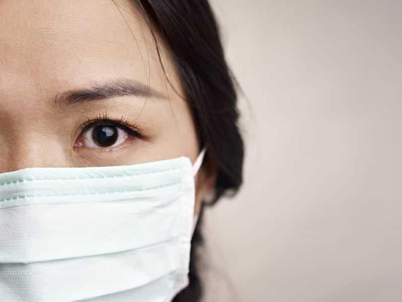 Imagem aproximada de uma mulher de traços sino-asiáticos usando uma máscara de proteção.
