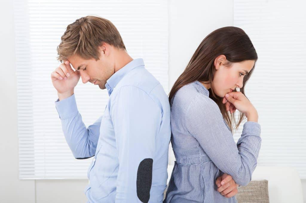 Homem e mulher de costas um para o outro, ambos com expressão séria e preocupada.