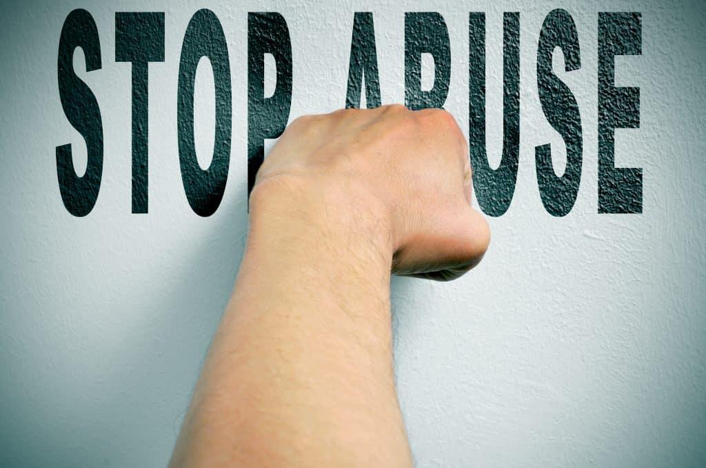 Imagem de um fundo branco e sobre ele está escrito em inglês a palavra STOP ABUSE - pare de abusar - e sobre a palavra a mão de um homem fechada.