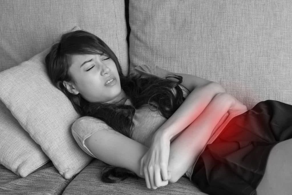 Imagem de uma mulher deitada no sofá. Ela está com um semblante de muita dor. Suas mãos estão sobre a região da barriga. Ela foi diagnosticada com a doença do útero baixo.