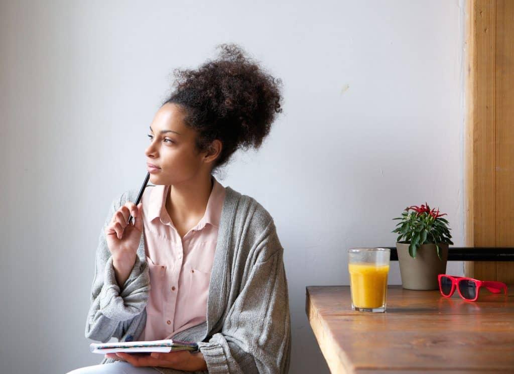 Mulher sentada na cadeira da cozinha segurando um caderno e olhando para o lado pensativa