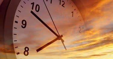 Ilustração de um relógio sobreposto ao pôr do sol.