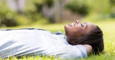 Mulher deitada em gramado com olhos fechados vista de perfil
