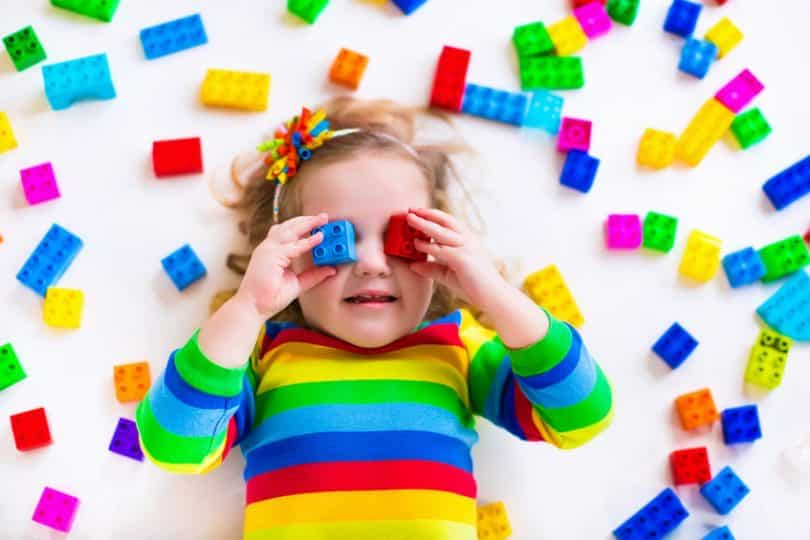 Criança segurando brinquedos coloridos vista de cima