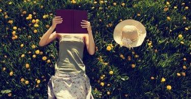Mulher deitada em um gramado com flores lendo um livro