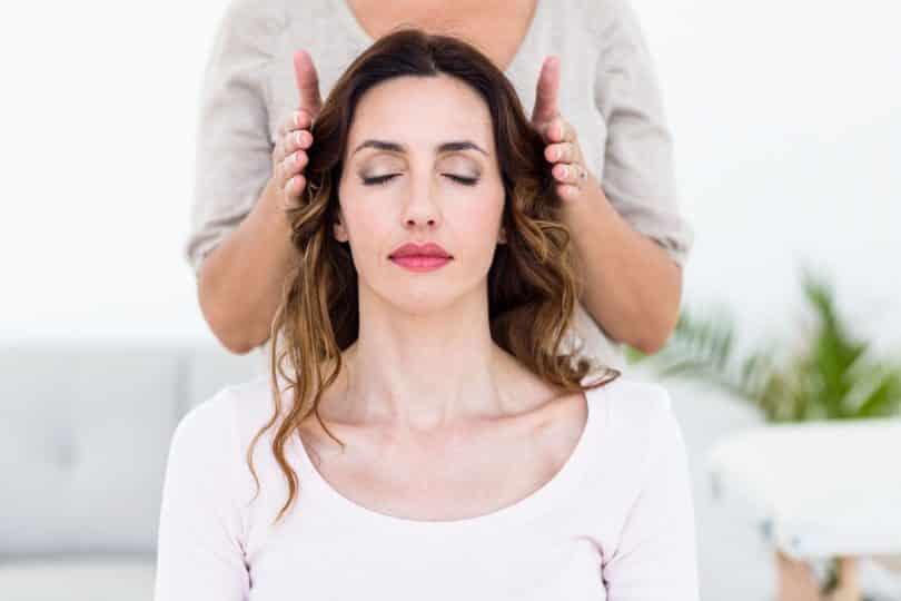 Mulher com os olhos fechados, e outra pessoa, atrás dela, tem as duas mãos aos lados da cabeça da mulher, sem encostar.