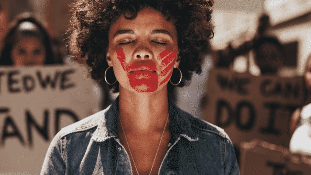 Mulher expressando violência de ser silenciada com mão vermelha pintada na boca