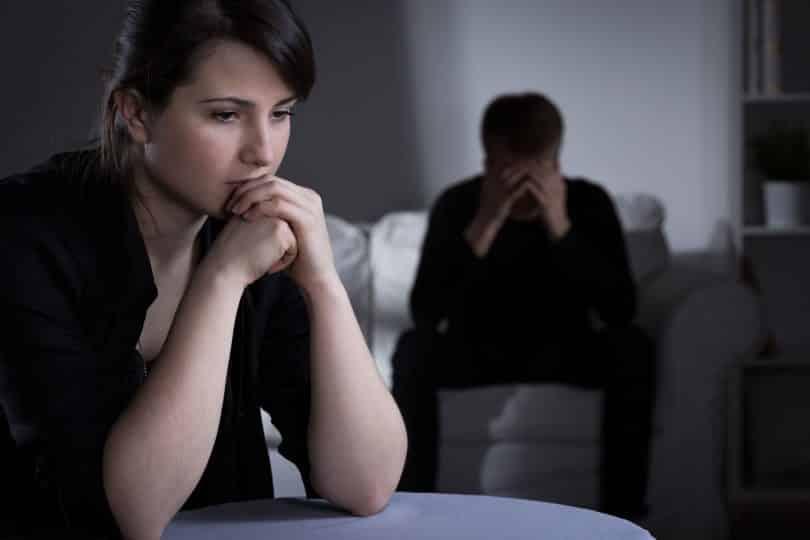 Mulhersentada em uma mesa em sua sala com as mãos em seu rosto preocupada enquanto homem está sentado em um sofá com as mãos no rosto