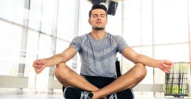 Homem sentado no chão, com as pernas cruzadas, meditando em espaço fechado, sem móveis, e com paredes de janelas.