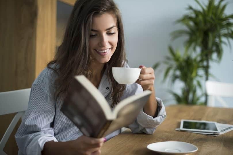 Mulher em sua mesa lendo livro e tomando café