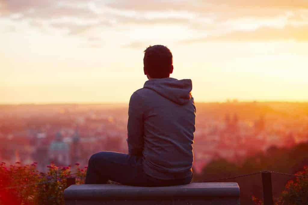 Homem sentado no topo de um prédio olhando para o pôr do sol