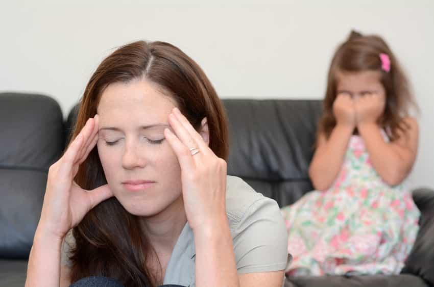 Mãe nervosa com filha chorando ao fundo da foto