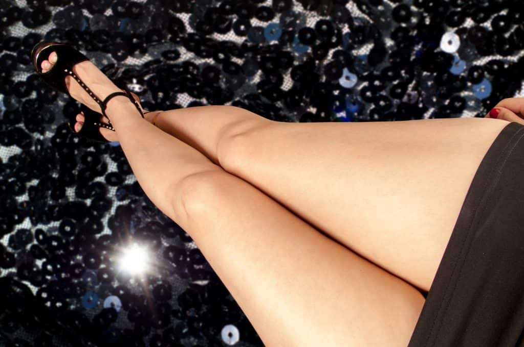 Imagem das pernas de uma mulher. Ela usa uma mini saia preta e um linda sandália de tiras também na cor preto.
