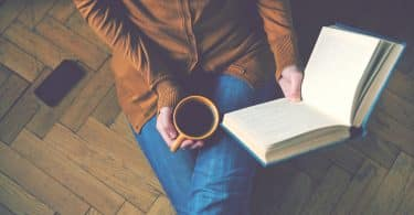 Mulher lendo livro segurando uma xícara de café