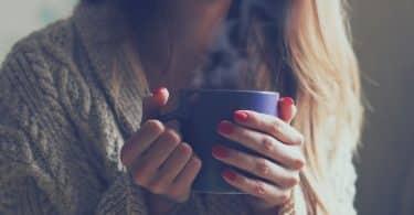 Mulher sorrindo segurando caneca de chá