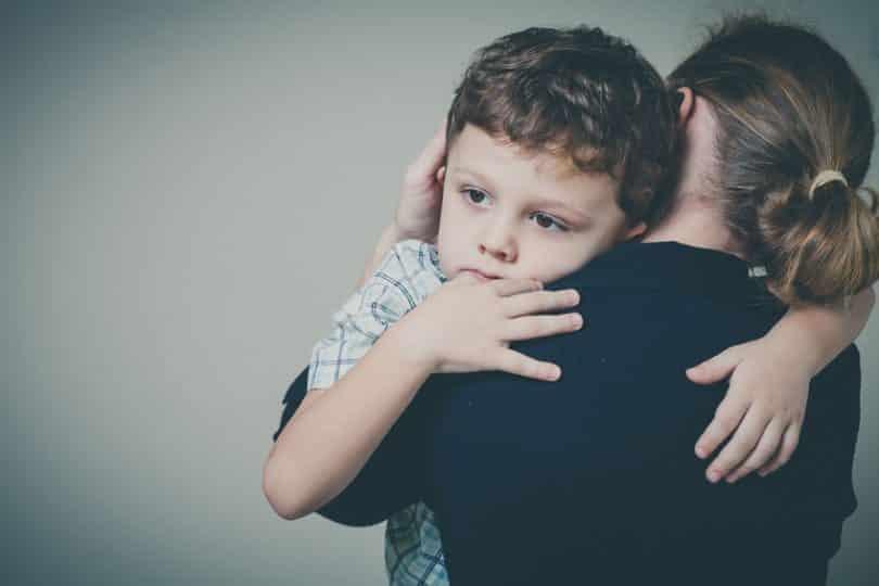 Mãe de costas com filho no colo com expressão triste