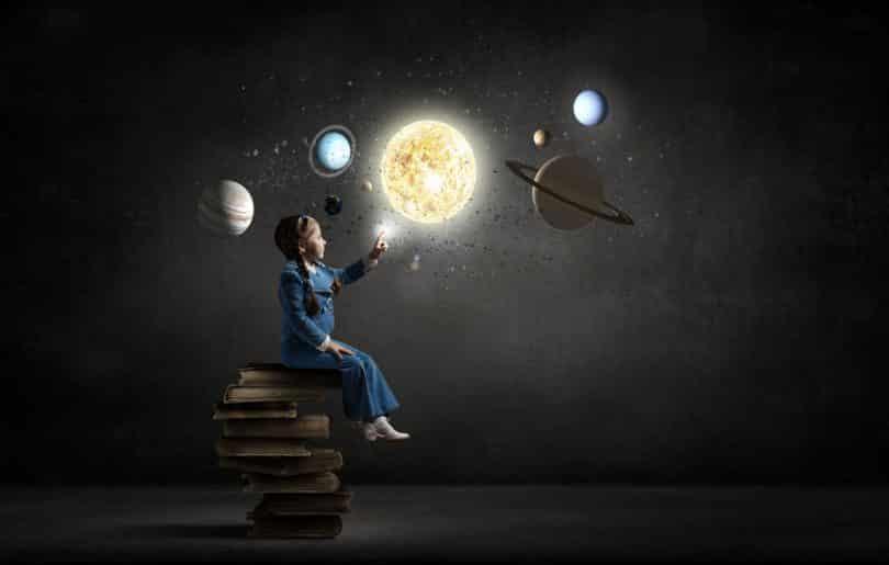 Menina sentada em pilha de livros com dedo em sistema solar e universo iluminados