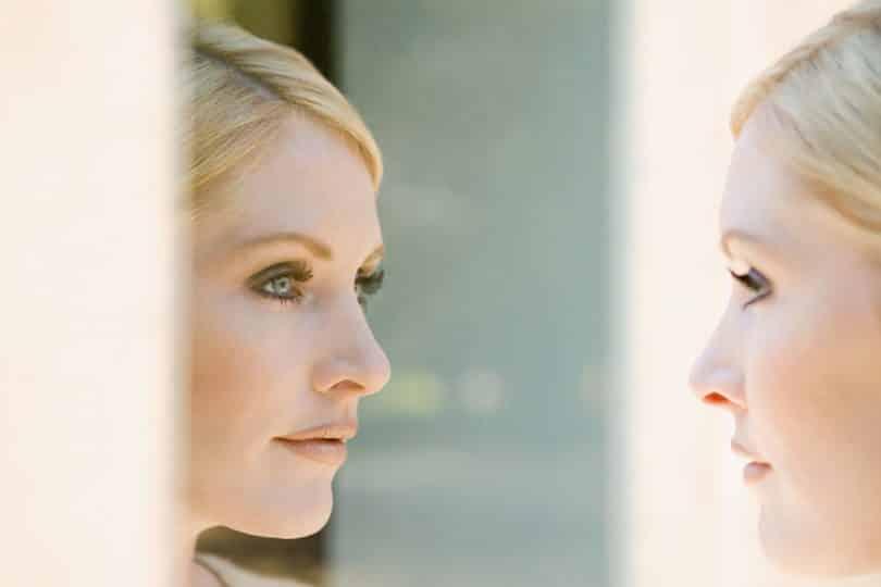 Mulher olhando seu reflexo no espelho.