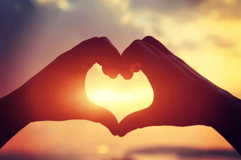 Mãos em formato de coração em frente ao pôr do sol.