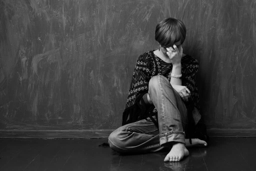 Imagem de uma mulher sentada no chão. Ela está triste, descalça, cabisbaixa e com uma das mãos cobrindo o seu rosto.