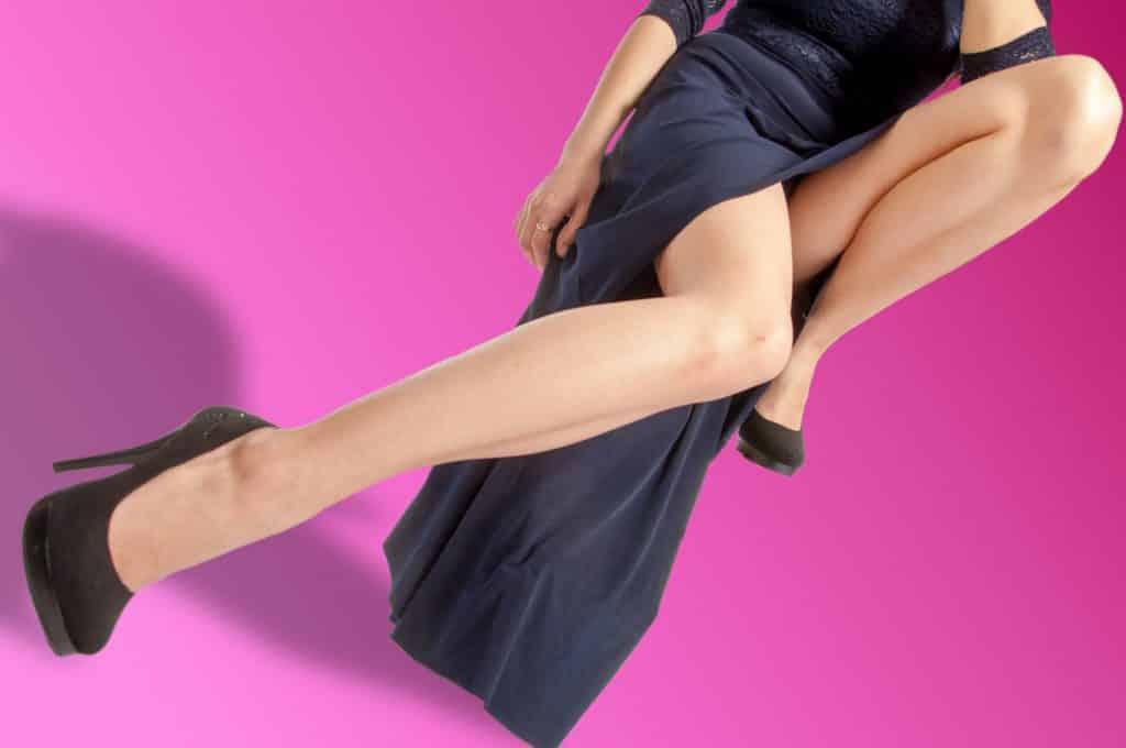 Imagem cpm fundo rosa com o corpo de uma mulher sentada em um banco e vestindo um lindo e longo vestido e um sapato de salto alto na cor preto.